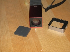 The Lytro camera. At left is the lens cover, it attaches magnetically. That's an item that will be lost immediately. Center, the camera, showing the front glass and lens. Right - a tripod adaptor.