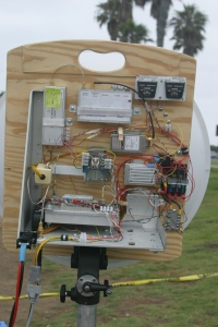 "Figure 5. The Farinon SSPA installed in ""Ms. June,"" my latest 10GHz rig. Two watts appears at the waveguide port at the antenna relay in transmit. The DC-DC converters are enclosed in separate chassis boxes, and can be seen just to the right of the amplifier. A re-labeled surplus meter monitors amplifier operation."