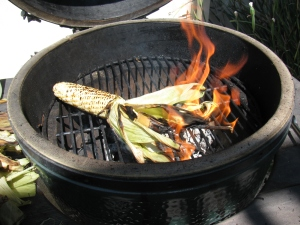 When corn husks catch fire - just let it burn off the silk and the husk - saves time later!